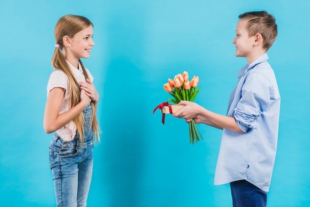 Vista lateral de un niño que da tulipanes y la caja actual a su amiga de pie contra el fondo azul