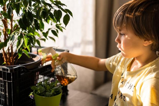 Vista lateral del niño regando las plantas.