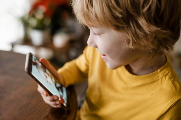 Vista lateral del niño sonriente con smartphone en casa