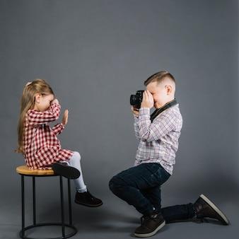 Vista lateral de un niño tomando fotos de una niña sentada en un taburete con cámara