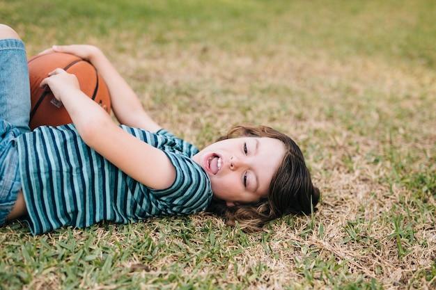Vista lateral del niño tumbado en la hierba