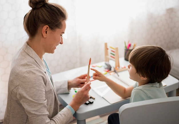 Vista lateral del niño y tutor en el aprendizaje en el hogar