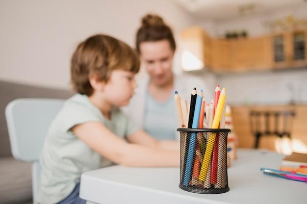 Vista lateral del niño y tutor en casa tomando una clase