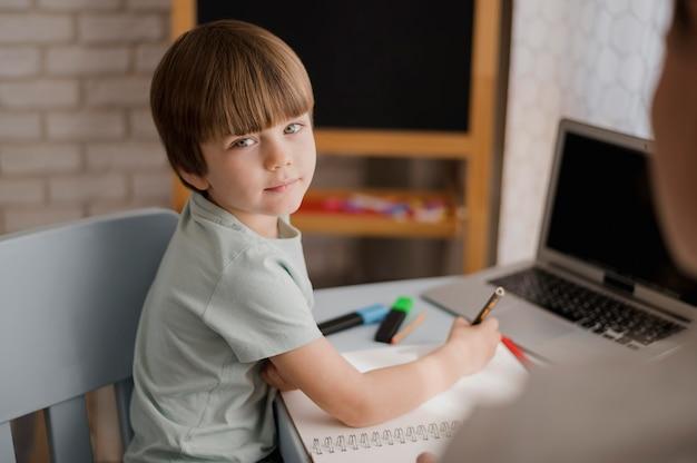 Vista lateral del niño tutorizado en casa con notebook y laptop