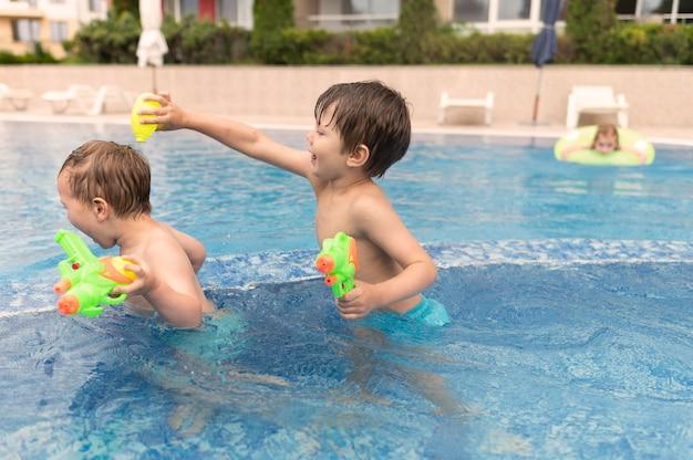 Vista lateral niños jugando en la piscina