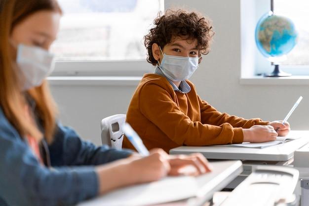 Vista lateral de niños con máscaras médicas en el aula de aprendizaje