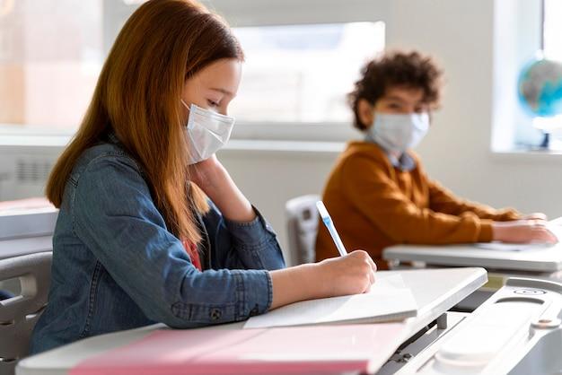 Vista lateral de los niños con máscaras médicas en el aula estudiando