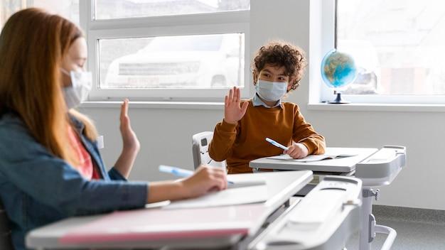 Vista lateral de niños con máscaras médicas en el aula saludándose desde la distancia