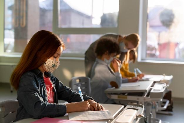 Vista lateral de los niños que aprenden en la escuela durante la pandemia