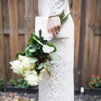 Vista lateral de la novia con rosas blancas y embrague