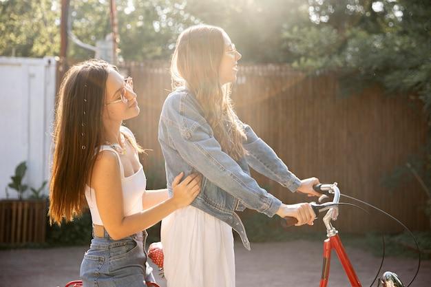 Vista lateral novias montando bicicleta juntos