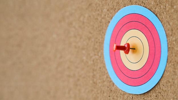 Vista lateral del objetivo colorido con alfiler en la diana