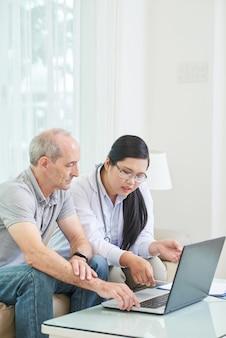 Vista lateral del paciente mayor navegando por la red en la computadora portátil con el médico