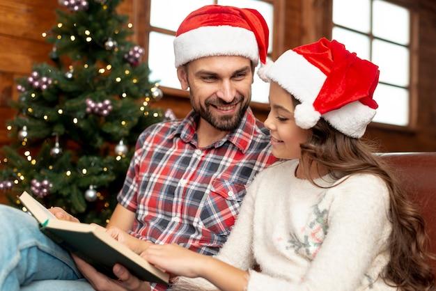 Vista lateral padre e hija leyendo