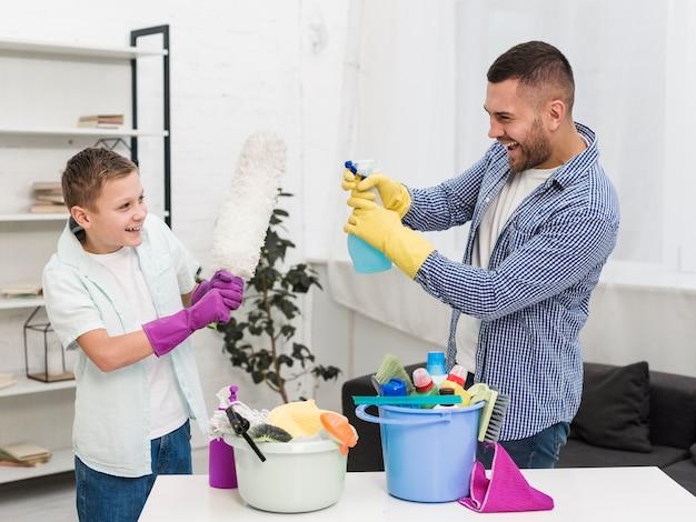Vista lateral de padre e hijo jugando mientras limpia la casa