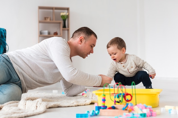 Vista lateral del padre jugando con niño