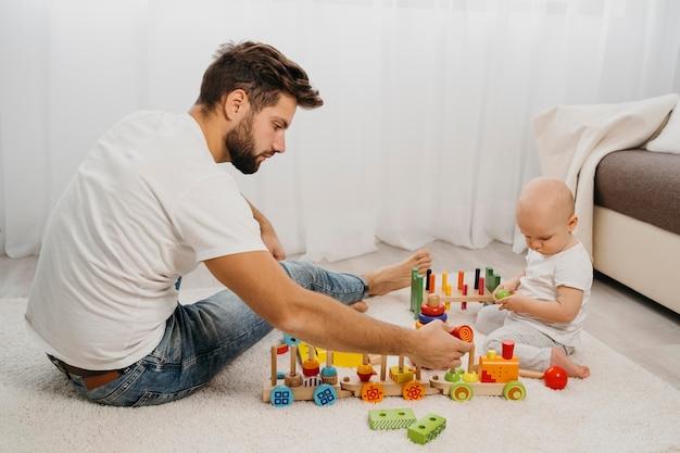 Vista lateral del padre jugando con su bebé
