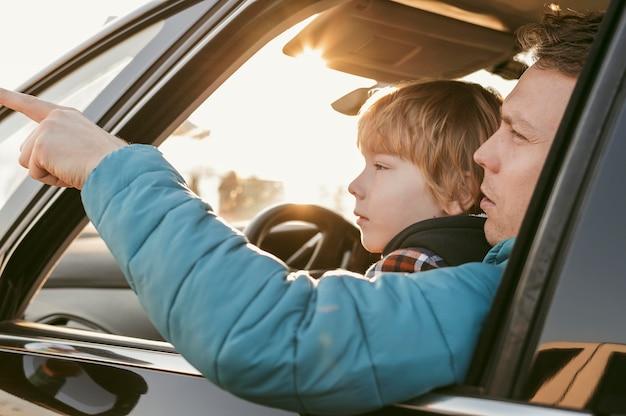 Vista lateral del padre y el niño en el coche durante un viaje por carretera