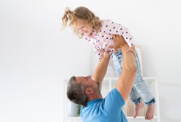 Vista lateral padre sosteniendo a su hijo