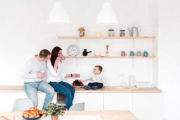 Vista lateral de padres con bebé en la cocina