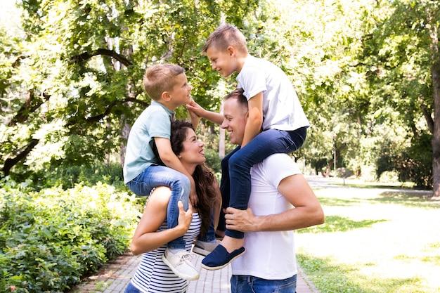 Vista lateral de los padres cargando a sus hijos.