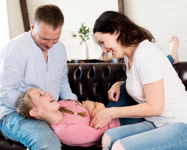 Vista lateral padres jugando con niña