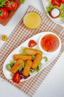 Vista lateral de palitos de queso frito con salsa sobre la mesa