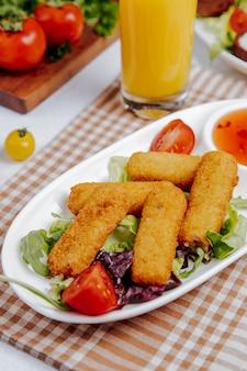 Vista lateral de palitos de queso frito sobre la mesa