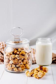 Vista lateral de palomitas de caramelo dulce en un frasco de vidrio sobre fondo blanco de madera