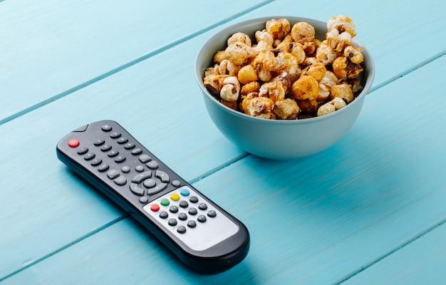 Vista lateral de palomitas de caramelo dulce en un recipiente y control remoto de televisión sobre fondo azul.