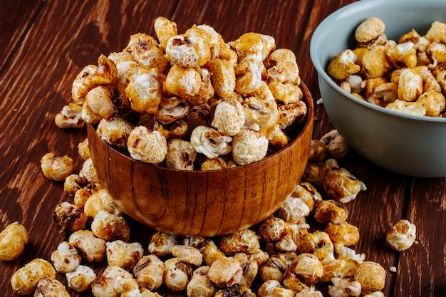 Vista lateral de palomitas de caramelo dulce en un tazón de madera sobre fondo rústico