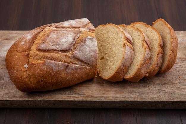 Vista lateral del pan crujiente cortado y en rodajas sobre la tabla de cortar sobre fondo de madera