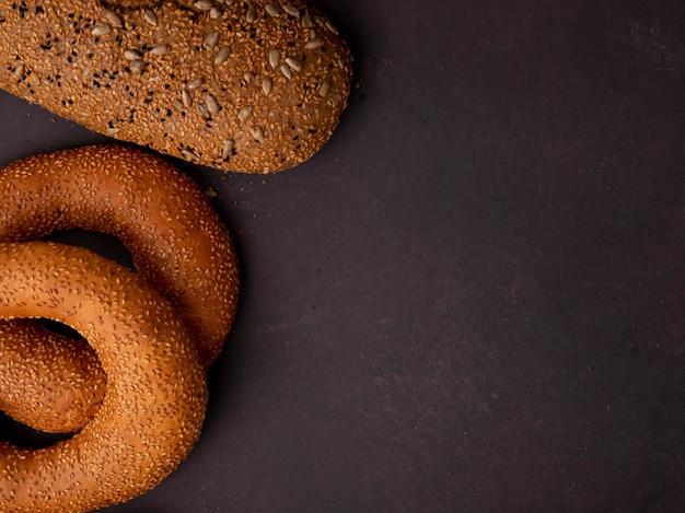 Vista lateral de panes como pan de bagel y sándwich en el lado izquierdo y fondo granate con espacio de copia