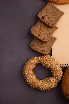 Vista lateral de panes como rebanadas de pan de bagel y centeno sobre fondo marrón con espacio de copia