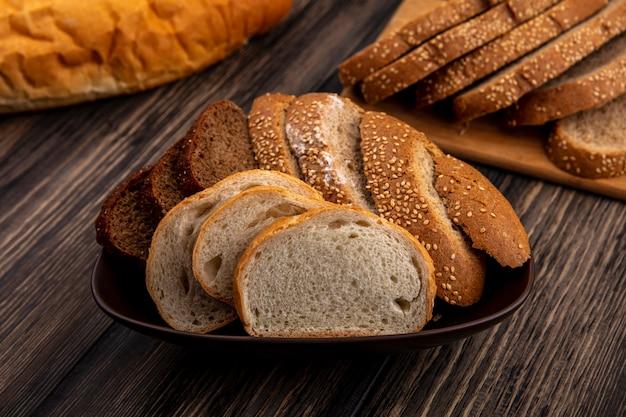 Vista lateral de los panes en rodajas de centeno mazorca marrón sin semillas y blancos en un tazón y en la tabla de cortar sobre fondo de madera
