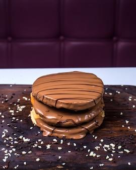 Vista lateral de panqueque con chocolate con leche sobre una plancha de madera