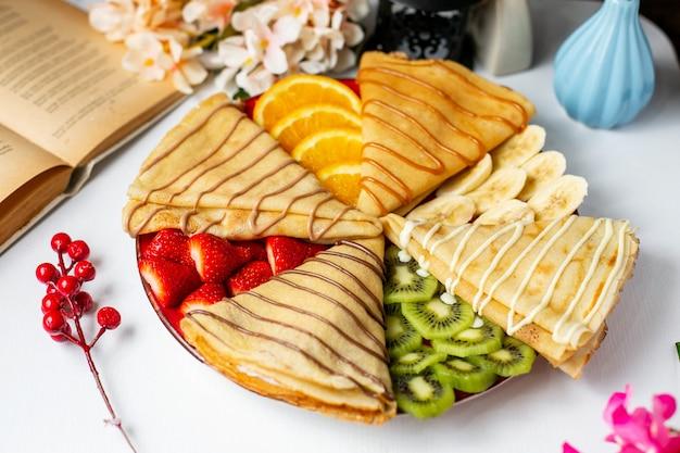 Vista lateral de panqueque con frutas y salsa de chocolate con leche sobre la mesa