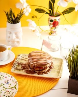 Vista lateral de panqueques cubiertos con chocolate con leche servido con té