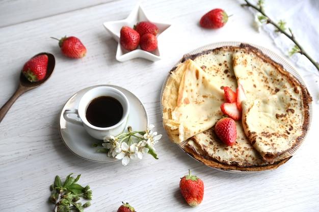 Vista lateral de panqueques con fresas y una taza de café