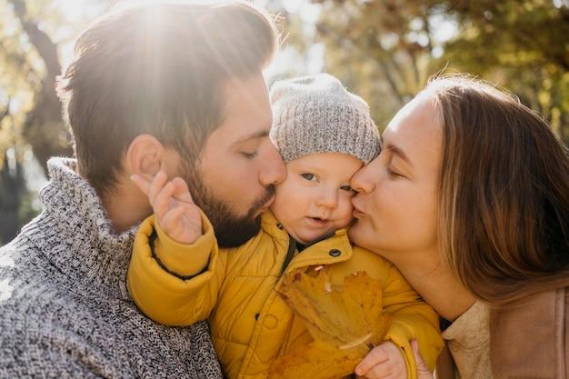 Vista lateral de papá y mamá con bebé afuera