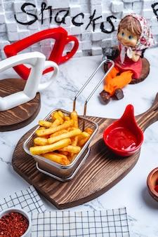 Vista lateral de papas fritas en una canasta con salsa de tomate en el tablero