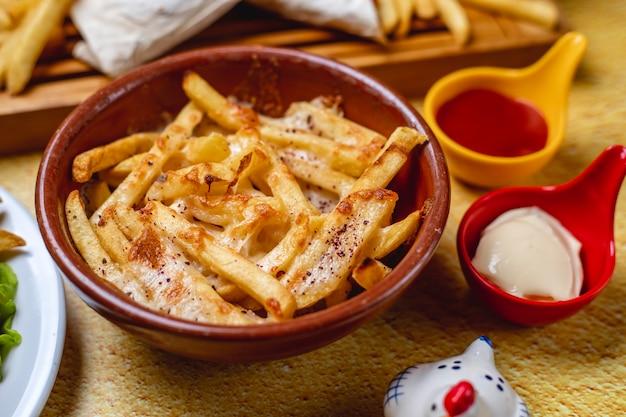 Vista lateral papas fritas con mayonesa de queso derretido y salsa de tomate sobre la mesa