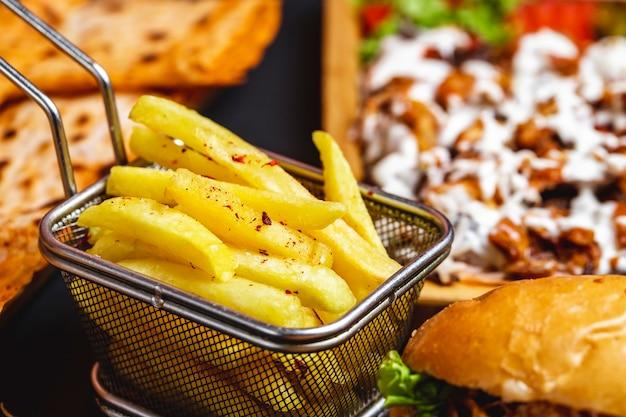 Vista lateral papas fritas en mini canasta de acero inoxidable con sal y hamburguesa sobre la mesa