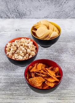 Vista lateral de papas fritas y palomitas de maíz en tazones sobre mesa de madera blanca vertical