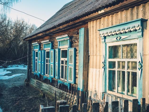 Vista lateral de la pared de una antigua casa de madera con ventanas y contraventanas azules.