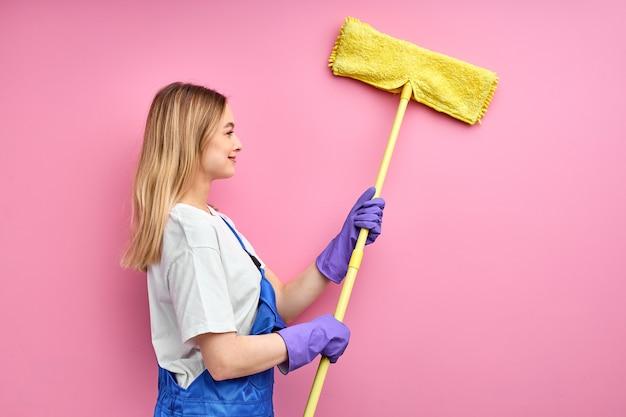 Vista lateral de la pared de limpieza de ama de casa con trapeador, joven bella dama en uniforme de trabajo azul y guantes de goma