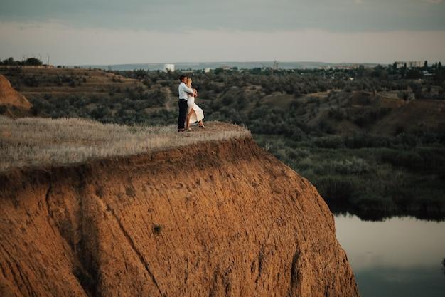 Vista lateral de la pareja abrazándose en la cima de la colina cerca del lago.