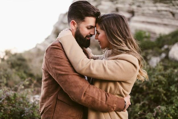 Vista lateral pareja abrazándose en la naturaleza