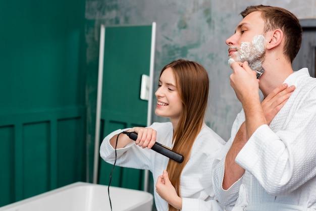 Vista lateral de la pareja de afeitarse y alisarse el cabello