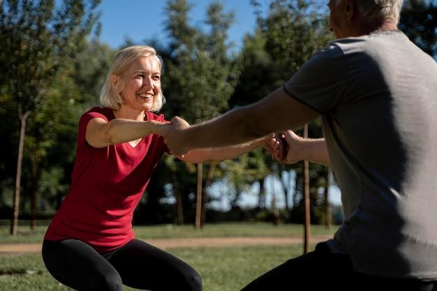 Vista lateral de la pareja de ancianos haciendo ejercicio al aire libre